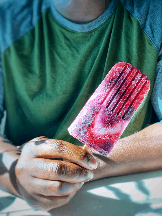 Man in green and grey tee-shirt seen from chest up. Holding a red, blue and white popsicle in right hand | Vegan Strawberry Blueberry and Cream Icicle pop | www.thevgnway.com