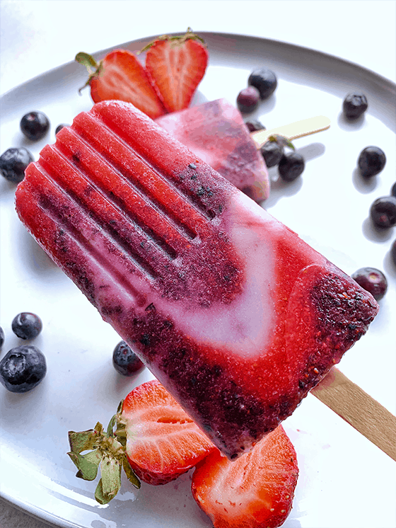 Grey plate on table with fresh blueberries scattered about and two strawberries cut in half. One red, blue and white Popsicle on plate and another Popsicle held above plate | Vegan Strawberry Blueberry and Cream Icicle pop | www.thevgnway.com