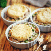 Three individual servings of jackfruit potpie filling in white ramekin each topped with golden biscuit