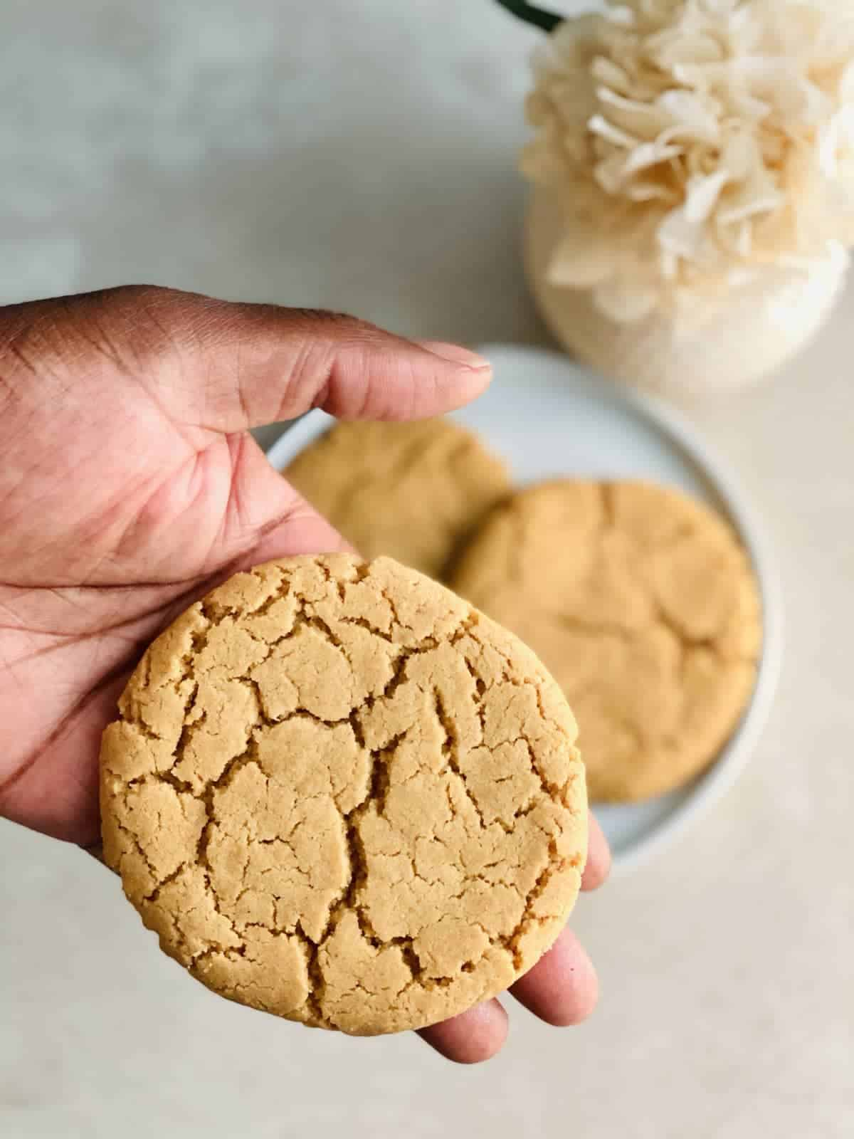 Hand holding one gluten-free peanut butter cookies over a white plate with two more cookies