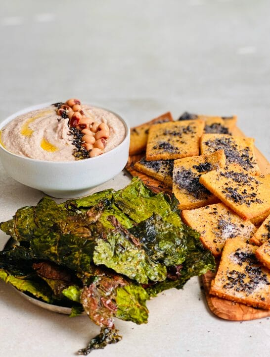 A dish of collard green chips surround by cornbread crackers on a wooden tray and a bowl of hummus topped with Black-eyes peas