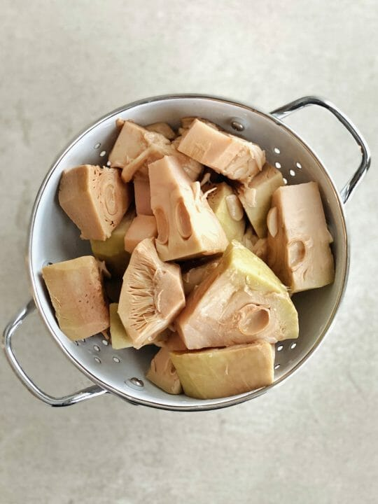 unripe canned jackfruit pieces in colander
