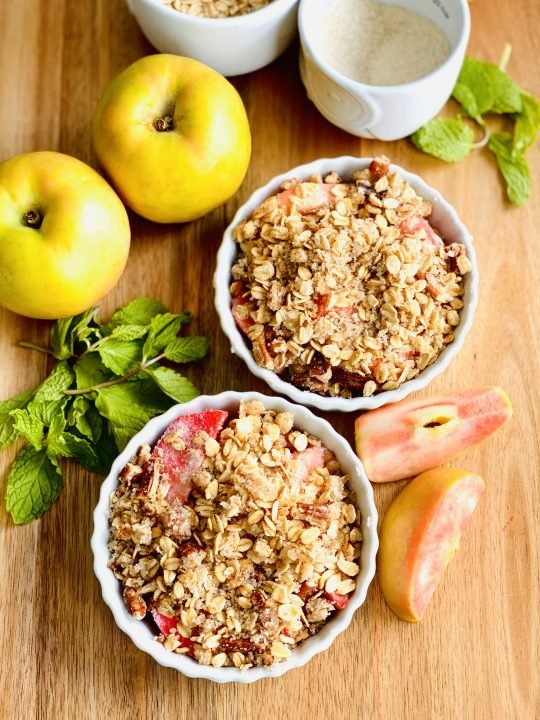2 apple crisp surrounded by apples and other ingredients
